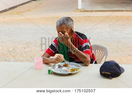 CHIANG RAI THAILAND - FEBRUARY 19 : unidentified old asian leprosy man with cap eating food on February 19 2016 in Chiang rai Thailand.
