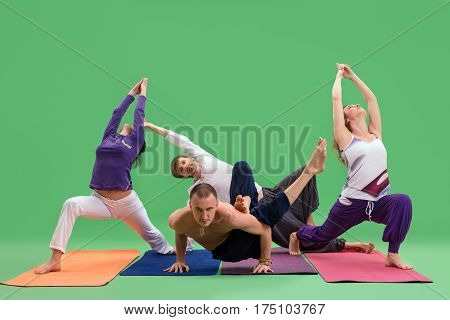 Men and women in bright sports clothes doing yoga on color mats in studio green background