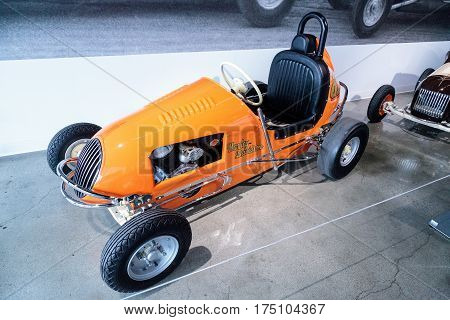 Los Angeles CA USA -- March 4 2017: Orange 1949 Unidentified three fourth midget racer powered by a Harley-Davidson engine at the Petersen Automotive Museum in Los Angeles California United States. Editorial only.