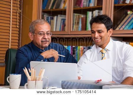 Two Indian senior and young businessmen discussing at the table together with laptop and paper, showing library in the background