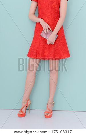 Woman in red sundress . Perfect female legs holding handbag-light blue background