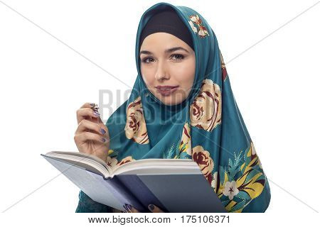 Female student author or journalist writing notes on a book with a pen. She is wearing a hijab associated with muslims or middle eastern and east european culture. The image depicts learning and education.