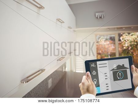 Digital composite image of hands holding digital tablet with home security icons