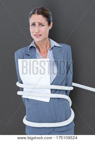 Businesswoman tied up in rope against grey background