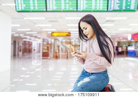 Asian woman sitting on the baggage use of mobile phone check in online ticket airline at international airport.