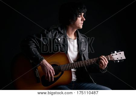 Rockstar in biker leather jacket playing solo on acoustic guitar.