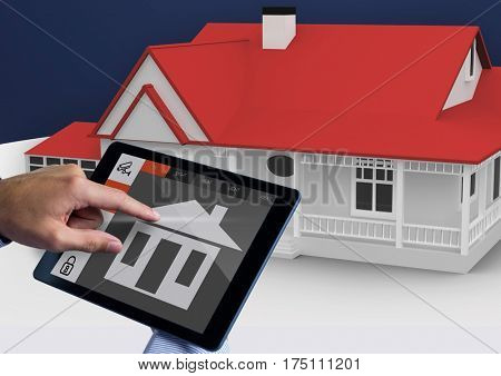 Digital composite image of hands using digital tablet with home security icons