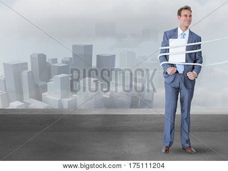 Digital composite image of businessman tied up in rope against cityscape