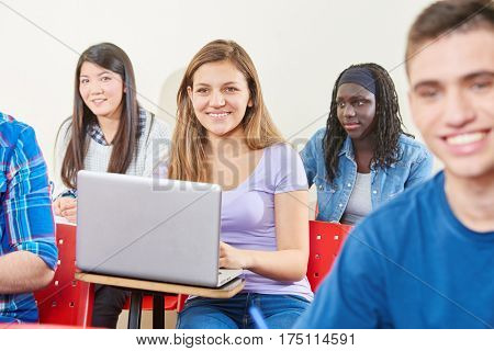 Girl learns with laptop in class with her interracial classmates