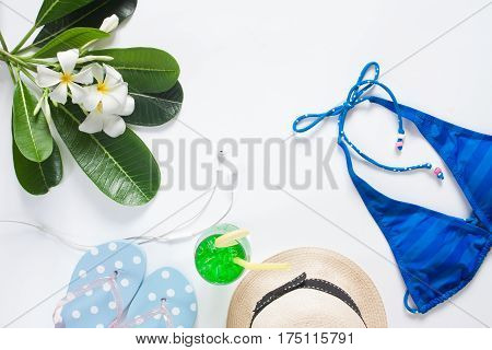 Overhead view of summer concept with blue stripe bikini sandal hat iced drink and plumeria flower Isolated on white background