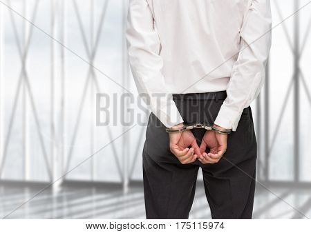 Rear view of guilty businessman with his hands cuffed against window in background