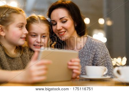 Little twins with touchpad and their mother having online entertainment