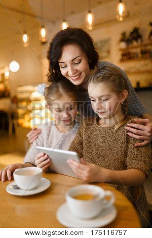 Young woman embracing her twin daughters with touchpad