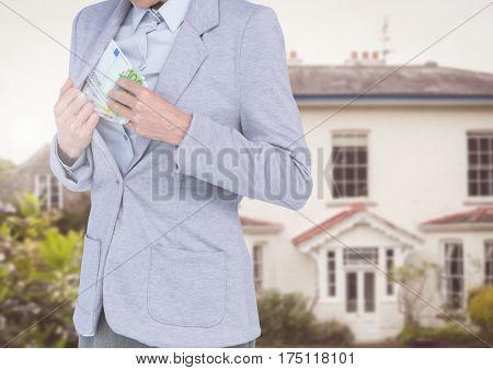 Composite image of corrupt businessman hiding money in blazer against house