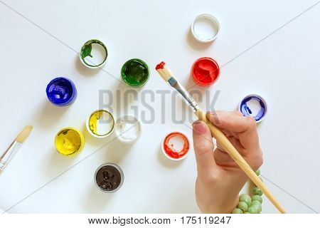 Hand of Artist holding wooden Brush and color Paints on white Table