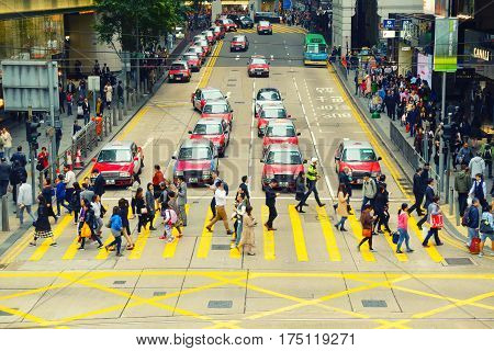 Hong Kong - February 23 2017: Business downtown of Hong Kong and crowded people accross the street.