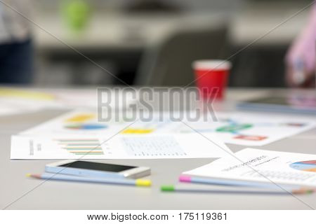 Solving Business Issue Concept - grey Office Table with Color professional Charts on Papers and Stationery dropped around color Pencils and Telephone