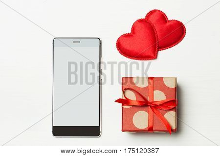 Phone and a gift for your loved one. Smartphone with a red bow and gift on a light wooden background decorated with hearts. The concept of the day of St. Valentine's weddings engagements Mother's Day birthday New Year Christmas holidays. Flat fly
