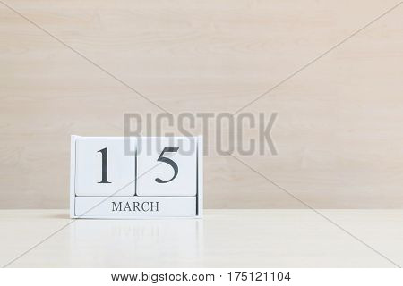 Closeup surface white wooden calendar with black 15 march word on blurred brown wood desk and wood wall textured background with copy space selective focus at the calendar