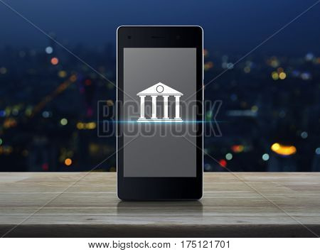 Bank icon on modern smart phone screen over blur colorful night light of city tower Mobile banking concept