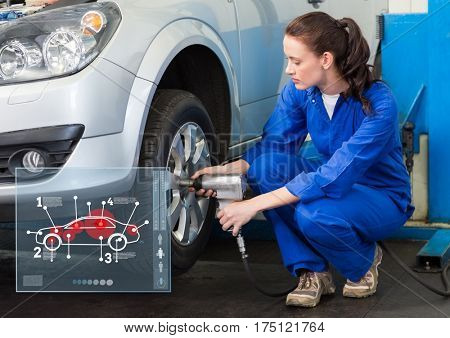 Digital composition of female mechanic working against car mechanics interface in background