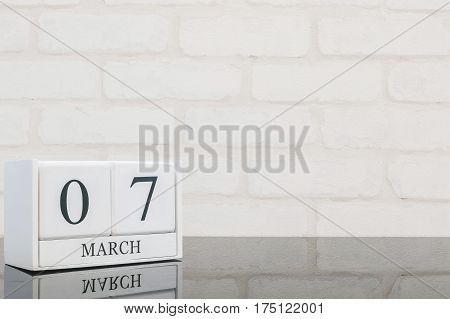 Closeup white wooden calendar with black 7 march word on black glass table and white brick wall textured background with copy space selective focus at the calendar