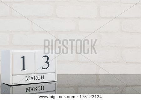 Closeup white wooden calendar with black 13 march word on black glass table and white brick wall textured background with copy space selective focus at the calendar