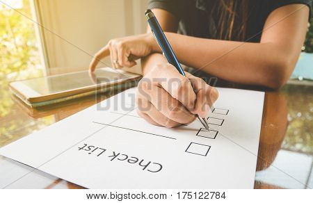close- up hand holding pen on check list paper with tablet in
