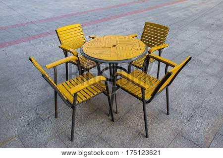 Yellow wooden table with a chain and padlock on the cement floor