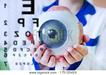Ophthalmology oculus sample closeup. Ophthalmology, eye model close-up. The ophthalmologist is holding a model of the eye. Chart test for ophthalmologist doctor