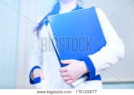 Young doctor girl with a folder of documents. Intern is the future physician treating people.