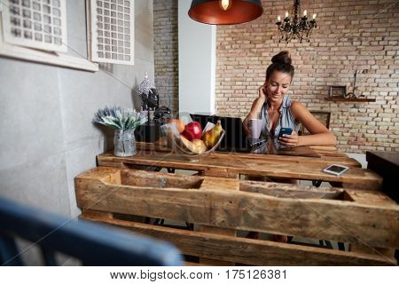 Young woman using mobile at trendy home.