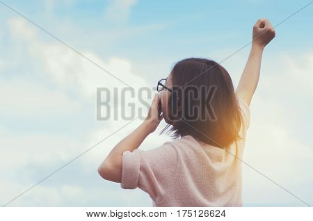 Relaxation Hapiness Early morning concept. Woman yawning with arms stretched on blue sky background.