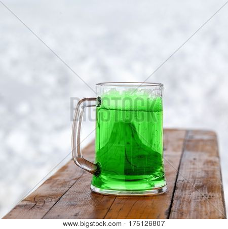 St. Patricks Day. Full fresh cold glass of green beer on wooden bench.