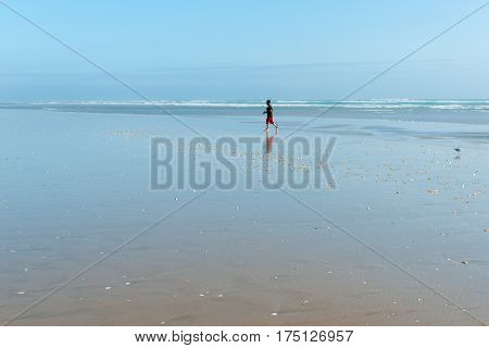 Ninety Mile Beach, New Zealand - February 13, 2017; Small distant figure of man walking along on wide flat sand by the sea at Ninety Mile beach Northland New Zealand