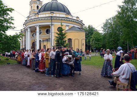 St. Petersburg Russia - May 22 2016: People in Russian national suits are dancing and playing at the festival of folk culture. Nicholas churchyard church of the prophet Eli in St. Petersburg 18th century.