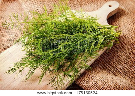 Fresh green dill on wooden cutting board on jute bag