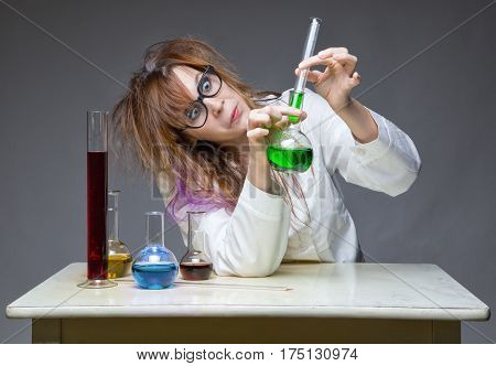 Working chemist with glass flask on gray background