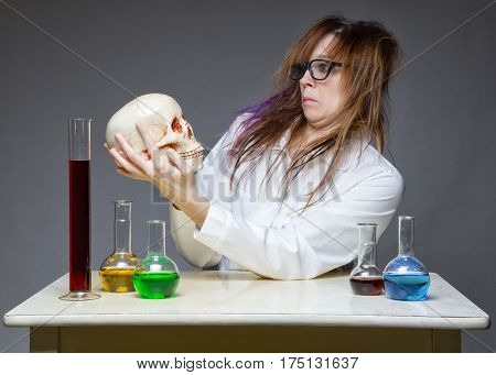 Surprised scientist with human skull on gray background