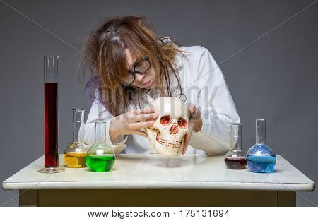 Looking for something scientist with human skull on gray background