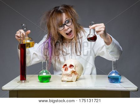 Happy scientist with human skull on gray background