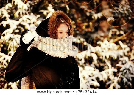 Young woman throwing snowball