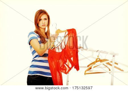 Teenager standing next to empty hanger and holding only blouse