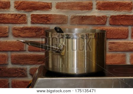 Steel saucepan on Electric Cooker and Red Exposed Brick Wall
