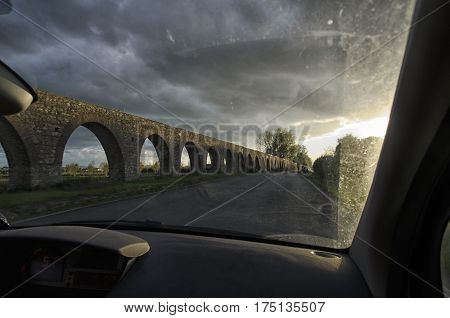 View of an aqueduct from dashboard of the car