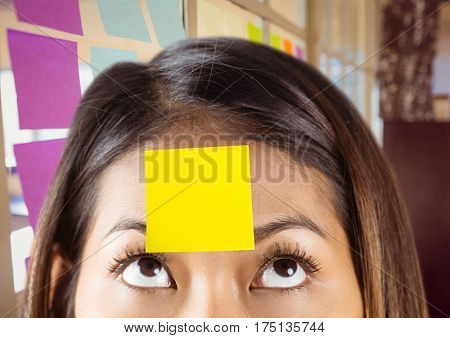 Close-up of woman with yellow sticky note on her forehead