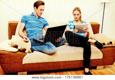 Young couple relaxing on sofa and using tablet and laptop