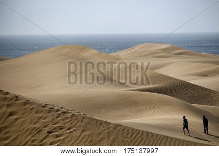 PLAYA DEL INGLÉS/SPAIN - 17 FEBRUARY 2017: People walking on the Maspalomas dunes in Gran Canaria with the ocean in the background. The sand is to make the dunes taken by clouds from Sahara desert