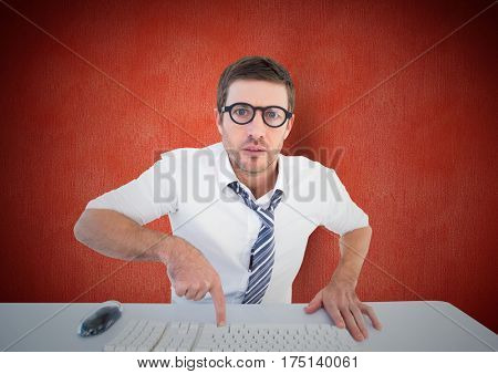 Portrait of a confused man pointing to computer keyboard at desk