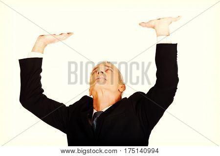 Businessman pushing invisible ceiling